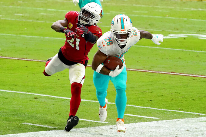 Miami Dolphins running back Salvon Ahmed (26) is knocked out of bounds by Arizona Cardinals cornerback Patrick Peterson (21) during the first half of an NFL football game, Sunday, Nov. 8, 2020, in Glendale, Ariz. (AP Photo/Rick Scuteri)