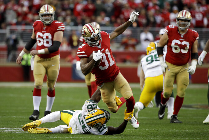 San Francisco 49ers running back Raheem Mostert is tackled by Green Bay Packers free safety Darnell Savage during the first half of the NFL NFC Championship football game Sunday, Jan. 19, 2020, in Santa Clara, Calif. (AP Photo/Marcio Jose Sanchez)