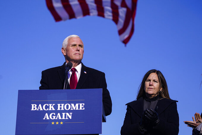 FILE - In this Jan. 20, 2021, file photo, former Vice President Mike Pence speaks after arriving back in his hometown of Columbus, Ind., as his wife Karen watches. Less than three months after former President Donald Trump left the White House, the race to succeed him is already beginning. Pence has started a political advocacy group, finalized a book deal and later this month in South Carolina will give his first speech since leaving office.  (AP Photo/Michael Conroy, File)