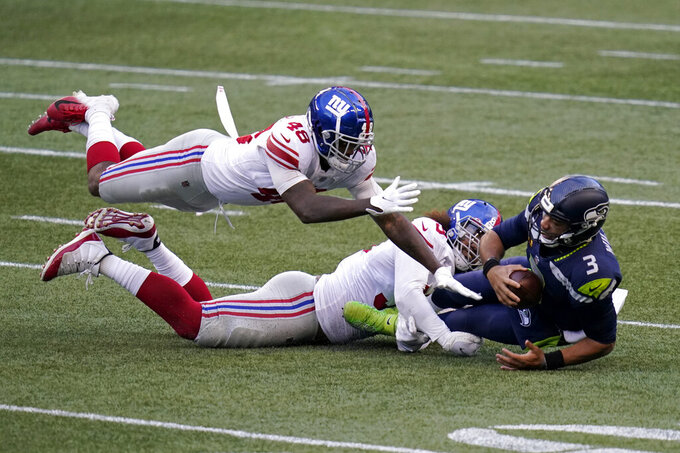 Seattle Seahawks quarterback Russell Wilson (3) is sacked by New York Giants defensive end Leonard Williams, center, as linebacker Tae Crowder (48) dives in to assist during the second half of an NFL football game, Sunday, Dec. 6, 2020, in Seattle. (AP Photo/Elaine Thompson)
