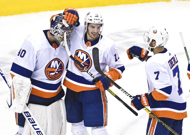 FILE - In this Aug. 20, 2020, file photo, New York Islanders goaltender Semyon Varlamov (40) celebrates his shutout win and series victory with teammates Mathew Barzal (13) and Jordan Eberle (7) after defeating the Washington Capitals in an NHL Stanley Cup playoff hockey game in Toronto. Islanders general manager Lou Lamoriello is focused on keeping his team intact by believing there's internal room for improvement after New York made its deepest playoff run in 27 years.  (Nathan Denette/The Canadian Press via AP)