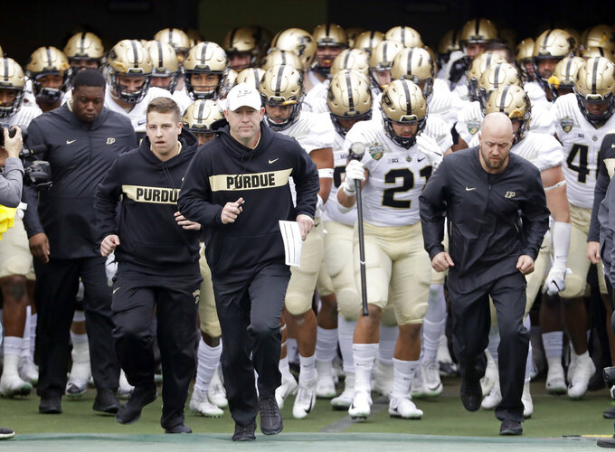 Purdue head coach Jeff Brohm, center, leads his team onto the field for the Magainst Auburn Friday, Dec. 28, 2018, in Nashville, Tenn. (AP Photo/Mark Humphrey)