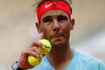Spain's Rafael Nadal prepares to serve against Mackenzie McDonald of the U.S. in the second round match of the French Open tennis tournament at the Roland Garros stadium in Paris, France, Wednesday, Sept. 30, 2020. Less than half a gram, or half the weight of a U.S. dollar bill. That is the tiny weight difference between the old French Open ball that Rafael Nadal happily bashed in winning his 12th title last year and the new one riling him in his chase for No. 13 at Roland Garros. The new ball is made by Chicago-based Wilson. (AP Photo/Christophe Ena)
