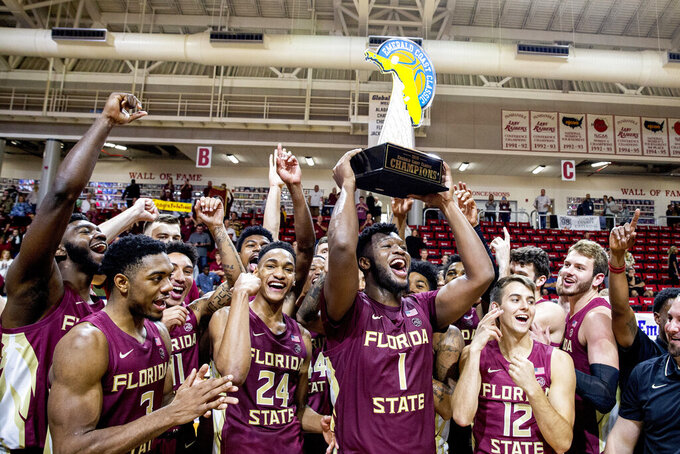 Florida State forward RaiQuan Gray (1) hoists the Emerald Coast Classic Championship trophy after Florida State defeated Purdue 63-60 in an NCAA college basketball game at the Emerald Coast Classic in Niceville, Fla., Saturday, Nov. 30, 2019. (AP Photo/Mark Wallheiser)