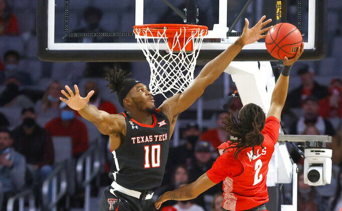 Texas Tech forward Tyreek Smith (10) blocks the shot of Houston guard Caleb Mills (2) during the first half of an NCAA college basketball game, Sunday, Nov. 29, 2020, in Fort Worth, Texas. (AP Photo/Ron Jenkins)