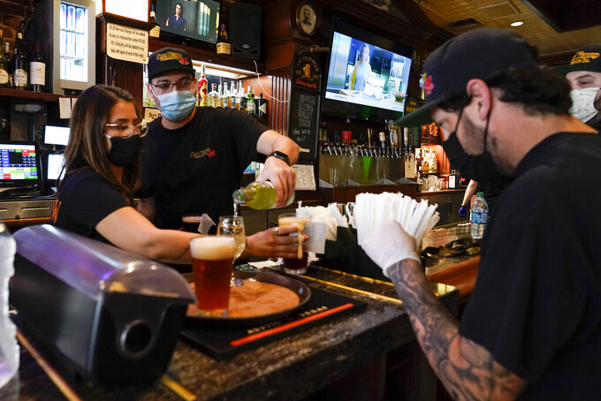 FILE - In this May 29, 2020, file photo, Jessica Ciaramitaro, Daryn Feenstra and Nicholas Soriano mix drinks while wearing face masks at the bar at San Pedro Brewing Company in the San Pedro area of Los Angeles. California will allow schools, day camps, bars, gyms, campgrounds and professional sports to begin reopening with modifications starting Friday, June 12, 2020. (AP Photo/Ashley Landis, File)