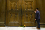 A man touches the door of the Supreme Court Friday, Sept. 18, 2020, in Washington, after the Supreme Court announced that Supreme Court Justice Ruth Bader Ginsburg has died of metastatic pancreatic cancer at age 87. (AP Photo/Alex Brandon)