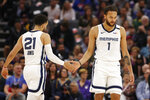 Memphis Grizzlies Tyus Jones, left, slaps palms with Kyle Anderson, right, as Anderson goes to the free-throw line during the first quarter of the team's NBA basketball game against the Sacramento Kings in Sacramento, Calif., Thursday, Feb. 20, 2020. (AP Photo/Rich Pedroncelli)