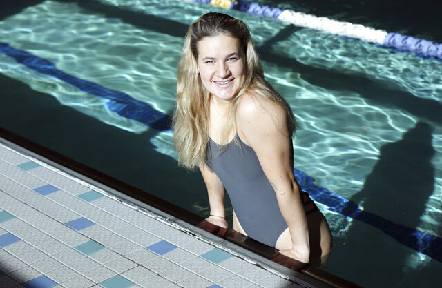Triathlete Parker Albright, 18, poses in the pool during a photo shoot at the YMCA in Salem, Va., on Jan. 22, 2020. Albright has recovered from a rough patch and is looking forward to competing in her sport at the University of South Dakota. (Heather Rousseau/The Roanoke Times via AP)