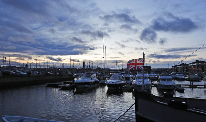 A British Union flag flutters in the breeze boats line the Marina in Hartlepool, England, Monday, Nov. 11, 2019. Political parties in Britain's Brexit-dominated December election are battling to win working-class former industrial towns, where voters could hold the key to the prime minister's office. The English port town of Hartlepool is an example. People there have long felt ignored by politicians in far-off London. (AP Photo/Frank Augstein)