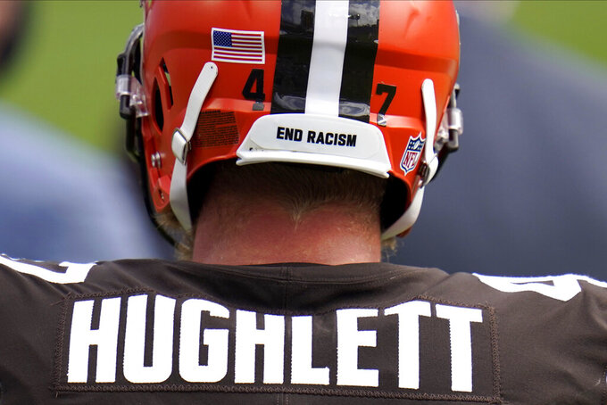 """End racism"" is seen written on the helmet of Cleveland Browns long snapper Charley Hughlett as he stands on the sidelines during the second half of an NFL football game against the Baltimore Ravens, Sunday, Sept. 13, 2020, in Baltimore. The Ravens won 38-6. (AP Photo/Julio Cortez)"