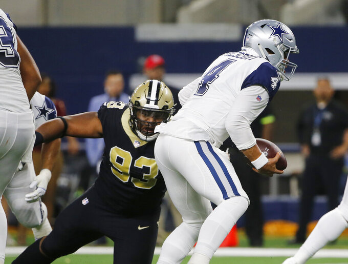 FILE - In this Nov. 29, 2018, file photo, Dallas Cowboys quarterback Dak Prescott (4) is pressured by New Orleans Saints defensive tackle David Onyemata (93) in the first half of an NFL football game, in Arlington, Texas. Onyemata has returned from suspension not a moment too soon for New Orleans' defensive front. (AP Photo/Michael Ainsworth, File)