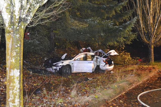 In this photo provided by the Corvallis Police Department is the scene where an Oregon man crashed a Tesla while going about 100 mph, destroying the vehicle, a power pole and starting a fire when some of the hundreds of batteries from the vehicle broke windows and landed in residences in Corvallis, Ore., on Tuesday, Nov. 17, 2020. Corvallis Police Lt. Ryan Eaton says Dylan Milota was driving a 2019 Tesla S Tuesday night when he lost control, left the road and hit a power pole. (Corvallis Police Department via AP)