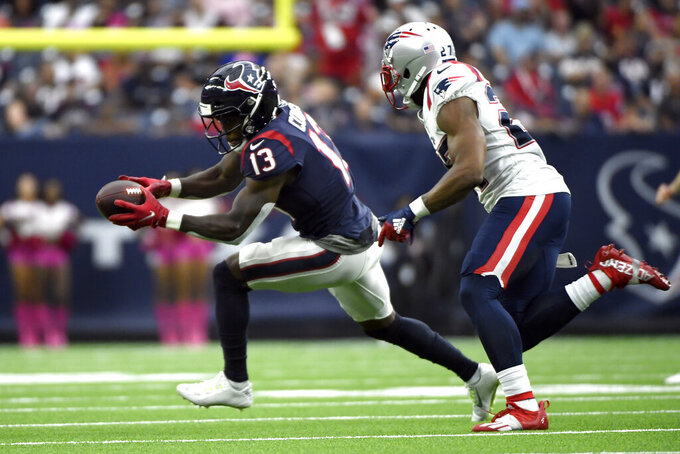 Houston Texans wide receiver Brandin Cooks (13) catches a pass as New England Patriots cornerback J.C. Jackson (27) defends during the second half of an NFL football game Sunday, Oct. 10, 2021, in Houston. (AP Photo/Justin Rex)