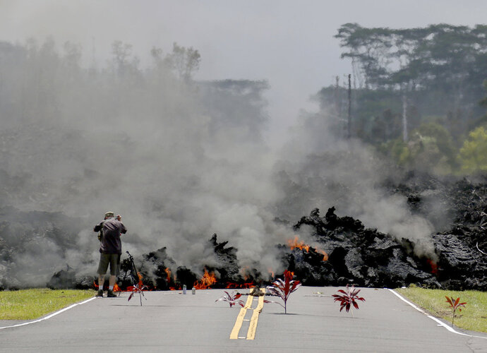 FILE - In this May 5, 2018 file photo, offerings of ti leaves, rocks and cans to the fire goddess Pele, lie in front of lava as it burns across a road in the Leilani Estates subdivision as an unidentified person takes pictures of the flow near Pahoa, Hawaii. When residents of rural Hawaii neighborhoods where lava from Kilauea volcano has burned down or threatened to consume their homes, a name often comes up: Pele. Pele, known as the goddess of volcanoes and fire, is an important figure in Hawaiian culture. (AP Photo/Caleb Jones, File)