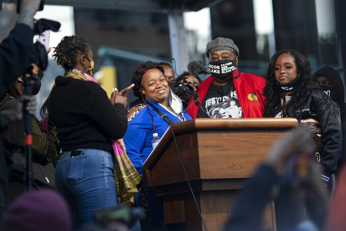 """Tamika Palmer, center, the mother of Breonna Taylor, stands on stage during the """"State of Emergency"""" rally calling for justice in Taylor's shooting, Saturday, Oct. 17, 2020, in New York. (AP Photo/Wong Maye-E)"""