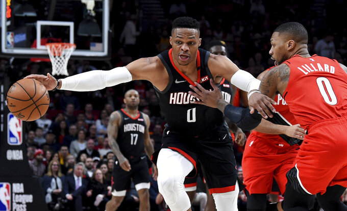 FILE - In this Jan. 29, 2020, file photo, Houston Rockets guard Russell Westbrook, left, dribbles next to Portland Trail Blazers guard Damian Lillard, right, during the first half of an NBA basketball game in Portland, Ore. Westbrook said Monday, July 13, 2020, that he has tested positive for coronavirus, and that he plans to eventually join his team at the restart of the NBA season. Westbrook made the revelation on social media. As recently as Sunday, the Rockets believed that Westbrook and James Harden — neither of whom traveled with the team to Walt Disney World near Orlando last week — would be with the team in the next few days. In Westbrook's case, that now seems most unlikely. (AP Photo/Steve Dykes, File)