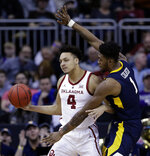 Oklahoma's Jamuni McNeace (4) looks to pass under pressure from West Virginia's Derek Culver (1) during the first half of an NCAA college basketball game in the Big 12 men's tournament Wednesday, March 13, 2019, in Kansas City, Mo. (AP Photo/Charlie Riedel)
