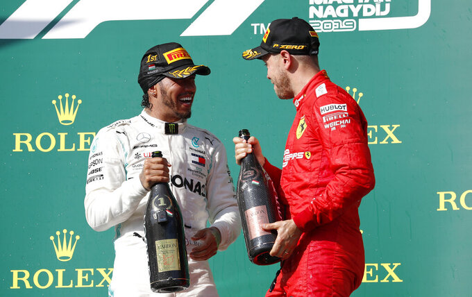 Mercedes driver Lewis Hamilton, left, of Britain, winner of the Hungarian Formula One Grand Prix, smiles on the podium with third placed Ferrari driver Sebastian Vettel, of Germany, at the Hungaroring racetrack in Mogyorod, northeast of Budapest, Hungary, Sunday, Aug. 4, 2019. (AP Photo/Laszlo Balogh)