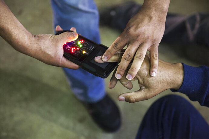 This undated photo obtained from Immigration and Customs Enforcement (ICE) shows a NeoScan 45 fingerprint scanner. The device, paired with an app known as EDDIE, is used by ICE to run remote ID checks. The app has been a core tool in President Donald Trump's deportation crackdown, according to a new report based on a Freedom of Information Act lawsuit. (Immigration and Customs Enforcement via AP)