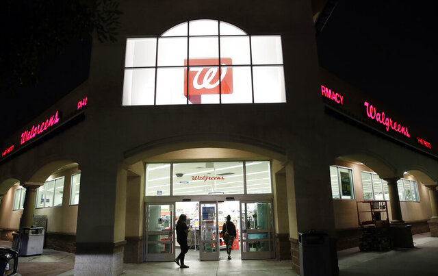 FILE - In this June 24, 2019 file photo, shoppers enter a Walgreens store in Los Angeles. Walgreens leader Stefano Pessina will step down as CEO and become executive chairman of the drugstore chain's board once they pick a new leader. The company also said Monday, July 27, 2020, that its current executive chairman, former McDonald's CEO Jim Skinner, will leave that role but remain on the board.   (AP Photo/Marcio Jose Sanchez, File)