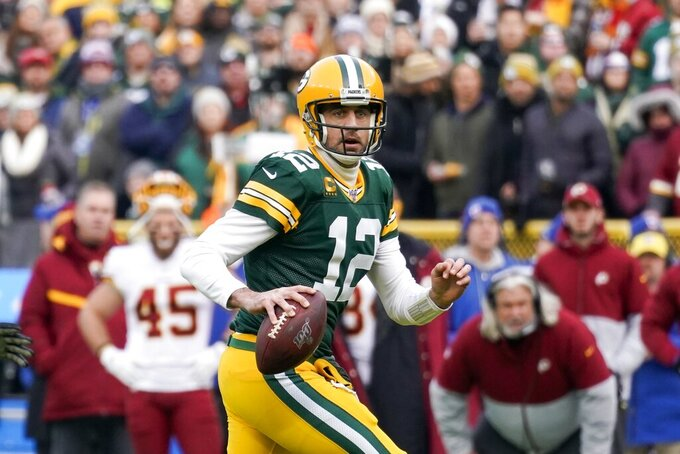 Green Bay Packers' Aaron Rodgers scrambles during the first half of an NFL football game against the Washington Redskins Sunday, Dec. 8, 2019, in Green Bay, Wis. (AP Photo/Morry Gash)
