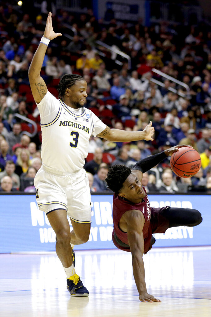 Montana's Michael Oguine, right, slips and falls against Michigan's Zavier Simpson (3) during the first half of a first round men's college basketball game in the NCAA Tournament in Des Moines, Iowa, Thursday, March 21, 2019. (AP Photo/Nati Harnik)