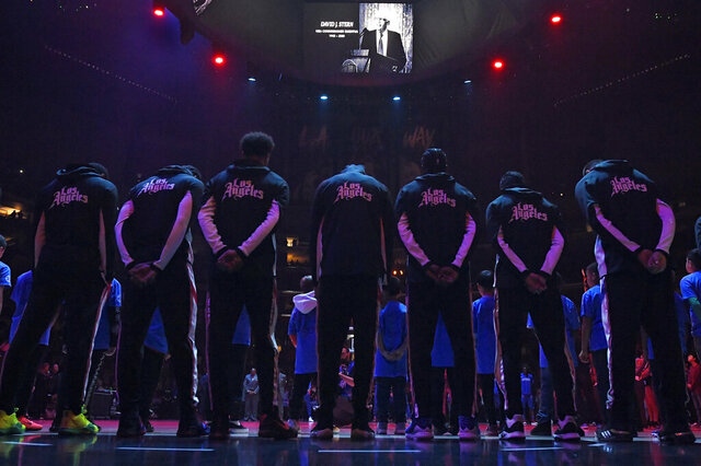 Members of the Los Angeles Clippers stand duringa a moment of silence Thursday, Jan. 2, 2020, in Los Angeles, prior to a basketball game against the Detroit Pistons, for former NBA Commissioner David Stern, who died Wednesday as a result of the brain hemorrhage. (AP Photo/Mark J. Terrill)
