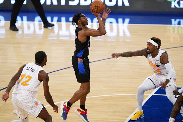New York Knicks guard Immanuel Quickley (5) goes up for a shot with Orlando Magic forward Gary Clark (12) and Magic guard Jordan Bone (23) reacting during the first half of an NBA basketball game, Monday, Jan. 18, 2021, in New York. (AP Photo/Kathy Willens, Pool)
