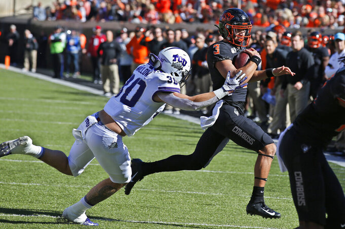 TCU linebacker Garret Wallow (30) chases Oklahoma State quarterback Spencer Sanders (3) in the first half of an NCAA college football game in Stillwater, Okla., Saturday, Nov. 2, 2019. (AP Photo/Sue Ogrocki)