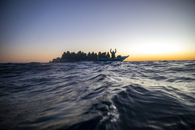 Migrants and refugees from different African nationalities wait for assistance aboard an overcrowded wooden boat, as aid workers of the Spanish NGO Open Arms approach them in the Mediterranean Sea, international waters, at 122 miles off the Libyan coast, Friday, Feb. 12, 2021. Various African migrants drifting in the Mediterranean Sea after fleeing Libya on unseaworthy boats have been rescued. In recent days, the Libyans had already thwarted eight rescue attempts by the Open Arms, a Spanish NGO vessel, harassing and threatening its crew in international waters.(AP Photo/Bruno Thevenin)
