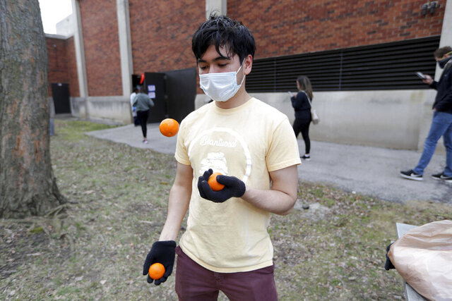 Isaac Repinski, of Milwaukee, juggles after voting at Riverside High School in Milwaukee on Tuesday, April 7, 2020. The Wisconsin primary is moving forward in the wake of the coronavirus epidemic after Gov. Tony Evers sought to shut down Tuesday's election in a historic move Monday that was swiftly rejected by the conservative majority of the Wisconsin Supreme Court by the end of the day. (Mike De Sisti/ Milwaukee Journal Sentinel via AP)