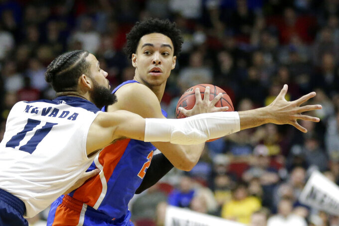 FILE - In this Thursday, March 21, 2019 file photo, Florida's Andrew Nembhard, right, is defended by Nevada's Cody Martin (11) during the second half of a first round men's college basketball game in the NCAA Tournament in Des Moines, Iowa. Florida point guard Andrew Nembhard is returning to school for his sophomore year, a move that should have a positive impact on the Gators next season. Nembhard announced his decision on social media Wednesday, hours before the deadline to withdraw from the NBA draft. (AP Photo/Nati Harnik, File)