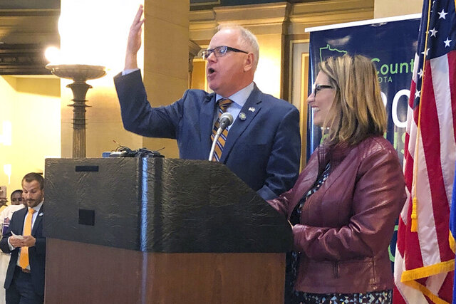 FILE - In this April 1, 2019 file photo, Minnesota Gov. Tim Walz, left, and Lt. Gov. Peggy Flanagan speak at the state Capitol in St Paul, Minn. Gov. Walz put himself into quarantine Monday, March 23, 2020, after a member of his security detail tested positive for COVID-19, the disease caused by the new coronavirus. The announcement followed an Instagram post by Lt. Gov. Peggy Flanagan late Sunday that her brother died of the disease in Tennessee. (AP Photo/Steve Karnowski File)