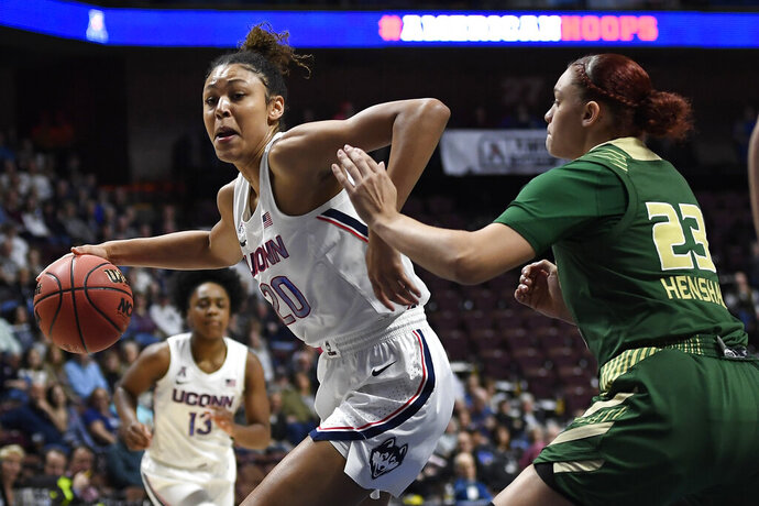 """FILE - Connecticut's Olivia Nelson-Ododa, left, drives around South Florida's Tamara Henshaw during the first half of an NCAA college basketball game in the American Athletic Conference tournament semifinals at Mohegan Sun Arena, Sunday, March 8, 2020, in Uncasville, Conn. UConn officials have discussed creating helmet stickers, warm-up T-shirts and altering athletic uniforms in other ways to show support for the Black Lives Matter movement. """"I believe as athletes that we have this platform, especially here, we have a platform and a voice and we should use it, especially on topics like this that have been going on for hundreds of years,"""