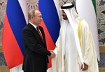 Russian President Vladimir Putin, left, and Abu Dhabi Crown Prince Mohamed bin Zayed al-Nahyan shake hands during the official welcome ceremony in Abu Dhabi, United Arab Emirates, Tuesday, Oct. 15, 2019. (Alexei Nikolsky, Sputnik, Kremlin Pool Photo via AP)