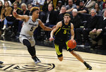 Oregon guard Chris Duarte, right, drives to the rim past Colorado guard D'Shawn Schwartz in the first half of an NCAA college basketball game Thursday, Jan. 2, 2020, in Boulder, Colo. (AP Photo/David Zalubowski)