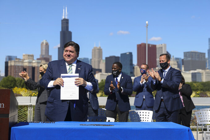 Gov. J.B. Pritzker holds up the state's Climate and Equitable Jobs Act after signing it at Shedd Aquarium in Chicago on Wednesday, Sept. 15, 2021. (Anthony Vazquez/Chicago Sun-Times via AP)