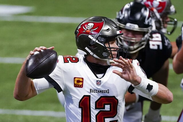 Tampa Bay Buccaneers quarterback Tom Brady (12) works in the pocket as Atlanta Falcons defensive tackle Tyeler Davison (96) gives pressure during the first half of an NFL football game, Sunday, Dec. 20, 2020, in Atlanta. (AP Photo/John Bazemore)