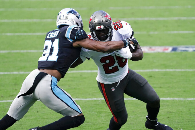 Tampa Bay Buccaneers running back Leonard Fournette (28) runs into Carolina Panthers strong safety Juston Burris (31) during the first half of an NFL football game, Sunday, Nov. 15, 2020, in Charlotte , N.C. (AP Photo/Gerry Broome)