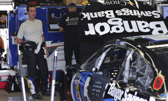 Austin Theriault sheds a layer of his fire suit his garage following a NASCAR Cup Series auto race practice at New Hampshire Motor Speedway in Loudon, N.H., Saturday, July 20, 2019. (AP Photo/Charles Krupa)