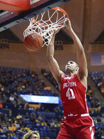 Boston University forward Sukhmail Mathon (41) dunks during the first half of the team's NCAA college basketball game against West Virginia on Friday, Nov. 22, 2019, in Morgantown, W.Va. (AP Photo/Kathleen Batten)
