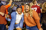 Auburn fans celebrate as other fans rush the field following an upset of Alabama in an NCAA college football game, Saturday, Nov. 30, 2019, in Auburn, Ala. (AP Photo/Vasha Hunt)
