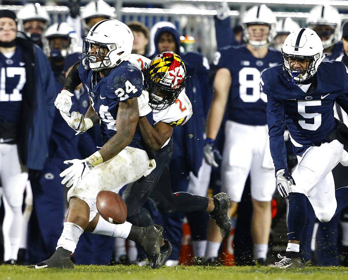 Maryland's RaVon Davis (2) strips the ball from Penn State's Miles Sanders (24) during the second half of an NCAA college football game in State College, Pa., Saturday, Nov. 24, 2018. Penn State won 38-3. (AP Photo/Chris Knight)