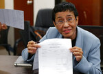 Maria Ressa, the award-winning head of a Philippine online news site Rappler that has aggressively covered President Rodrigo Duterte's policies, shows an arrest form after being arrested by National Bureau of Investigation agents in a libel case Wednesday, Feb. 13, 2019 in Manila, Philippines. Ressa, who was selected by Time magazine as one of its Persons of the Year last year, was arrested over a libel complaint from a businessman which Amnesty International has condemned as