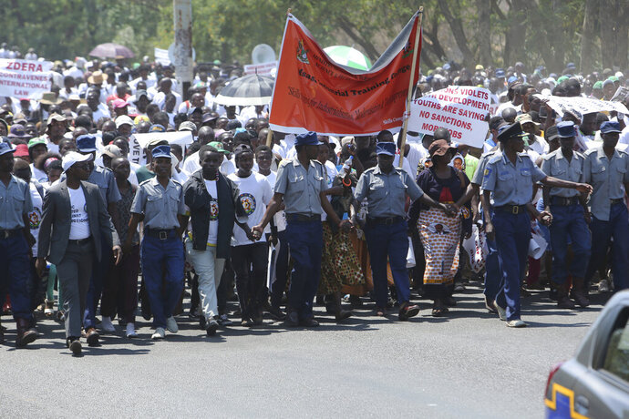 Hundreds of people march on the streets of Harare, Friday, Oct, 25, 2019, in protest over US sanctions that the Zimbabwean government blames for the country's worsening economic problems. The Zimbabwe government blames U.S. sanctions for devastating economic conditions, galloping inflation and severe shortages of basic goods, but the U.S denies the allegation and blames corruption, financial mismanagement and human rights violations instead. (AP Photo/Tsvangirayi Mukwazhi)
