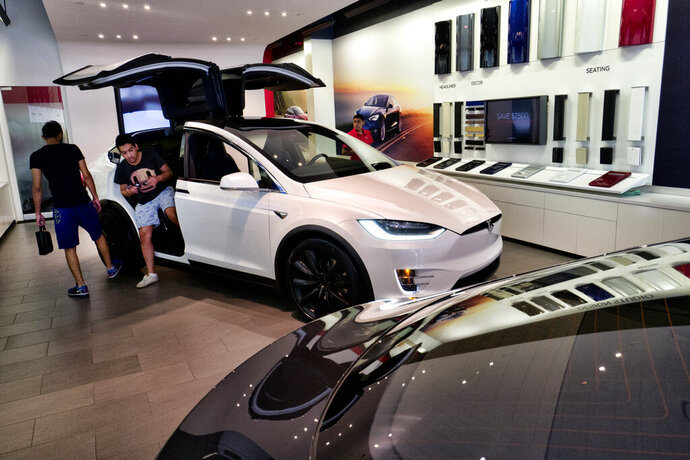 FILE - In this Aug. 8, 2018, file photo, customers check out the Tesla X, at the Tesla showroom in Santa Monica, Calif. California's rebate program to entice more drivers to purchase electric vehicles got less generous, especially for those looking to buy luxury models. Effective Tuesday, Dec. 3, 2019, regulators stopped offering rebates for electric cars or plug-in hybrids that cost more than $60,000. (AP Photo/Richard Vogel, File)