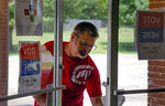 Jame Loe sanitizes the doors for voters at Canadian Hills Church of the Nazarene on Tuesday, June 30, 2020, in Oklahoma City, Okla. (Chris Landsberger/The Oklahoman, via AP)