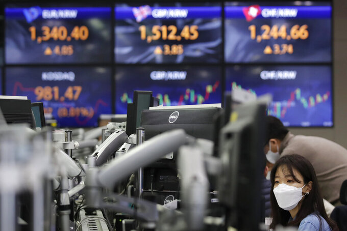 A currency trader watches computer monitors near the screens showing the foreign exchange rates at the foreign exchange dealing room in Seoul, South Korea, Friday, Jan. 22, 2021. Asian stock markets retreated Friday after a resurgence of coronavirus infections in China and a rise in cases in Southeast Asia.(AP Photo/Lee Jin-man)