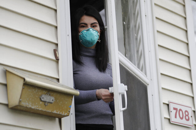 Francy Sandoval poses for a portrait at her home in Melrose Park, Ill., Thursday, April 23, 2020. She works as a receptionist at a community health clinic which treats multiple COVID-19 cases. She has to isolate herself in the attic as soon as she comes home from work each day and is terrified of infecting her family. (AP Photo/Nam Y. Huh)